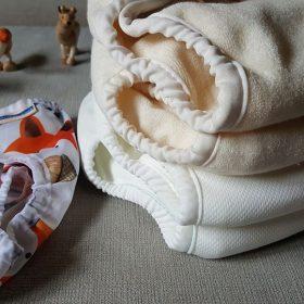 Hibridni sistem Mother ease Wizard Duo ... univerzalno velike nepremočljive hlačke na levi ter kupček različnih vložkov na desni - od spodaj navzgor si sledijo: stay dry nočni, stay dry, bombaž in bambus.